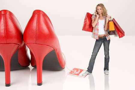 spendthrift: fair-haired girl  with shopping bags standing on table beside giant red pumps Stock Photo