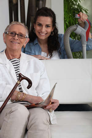 home health care: Young woman helping an elderly lady with her household chores
