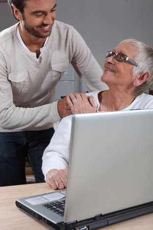 hand on shoulder: Son helping mother on laptop Stock Photo