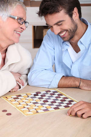 60 64 years: young man playing checkers with older woman