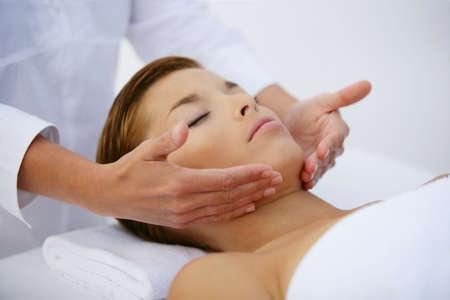tratamiento facial: Joven mujer de relax durante el masaje facial Foto de archivo