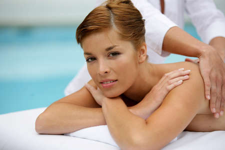 Woman receiving back massage by the pool Stock Photo - 12068816