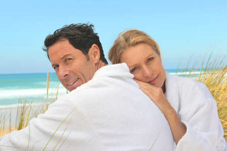 45 49 years: Couple on the dunes in towelling robes Stock Photo