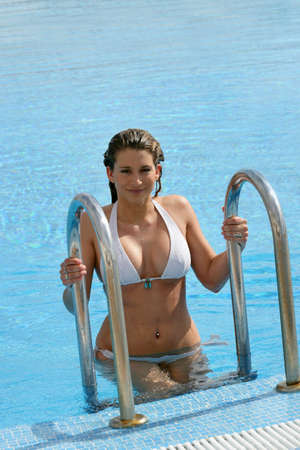 Gorgeous woman getting out of swimming pool