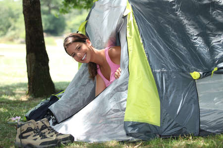 Young woman popping her head out of a tent photo