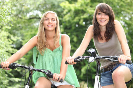 Two teenage girls riding bikes in the countryside photo