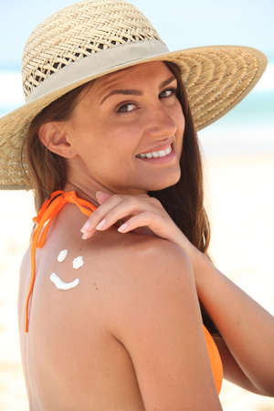 melanoma: woman with sunscreen on the beach wearing a hat