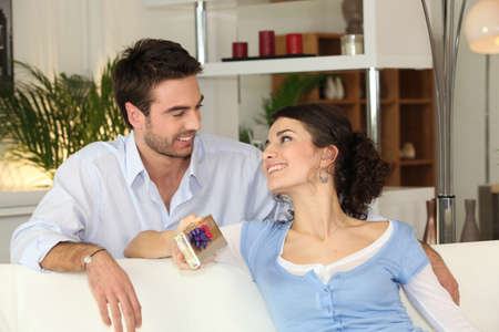 Man giving gift in living room Stock Photo - 12103696