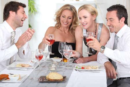 Cuatro personas alegres en el inicio de una cena elegante.