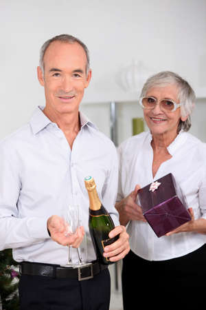 Older couple with champagne and a gift photo