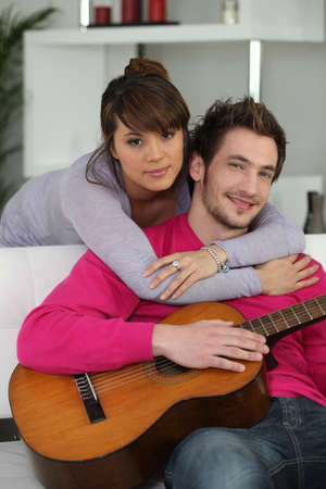 a guitarist boy playing guitar: Young couple indoors with a guitar