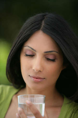 Indian woman drinking a glass of water photo