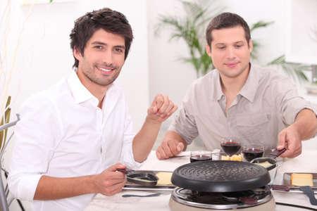 Men eating raclette photo