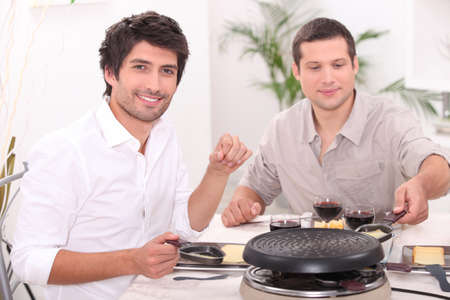 Men eating raclette photo