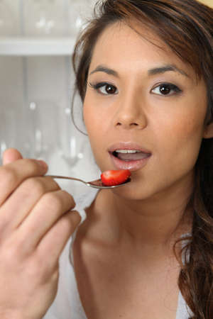 Asian woman eating strawberries photo