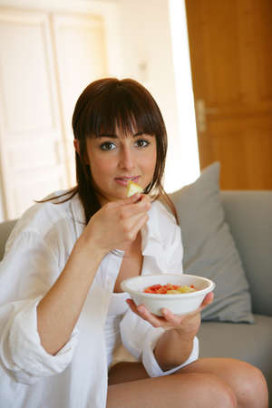 Portrait of a young woman eating a salad of fruits Stock Photo - 12008021