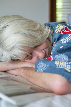 Old lady fell asleep whilst reading magazine photo