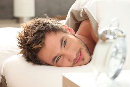 up wake: young man in bed waking up Stock Photo