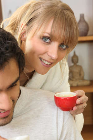 Woman drinking coffee next to husband photo