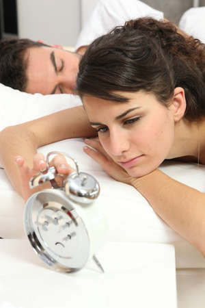 Woman waking up to an alarm clock photo