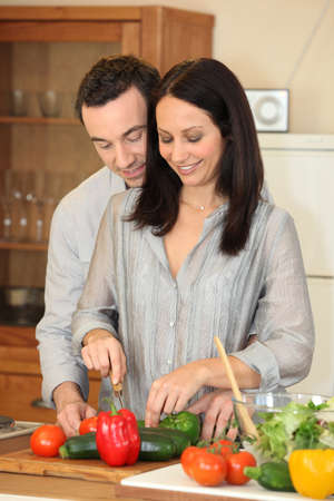 Couple cutting vegetables in a kitchen Stock Photo - 12103631