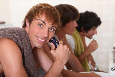 auburn hair: young men shaving and brushing teeth Stock Photo