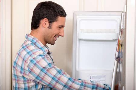 Man opening fridge door photo