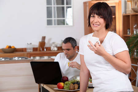 Woman drinking coffee while her husband looks at his laptop during breakfast photo