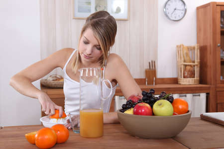 cute blonde pressing orange for breakfast Stock Photo - 12006069