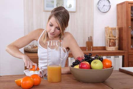 cute blonde pressing orange for breakfast Stock Photo - 12006069