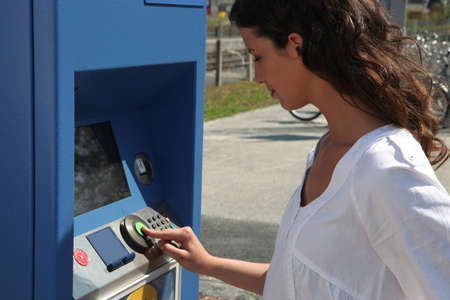 Woman using a ticket machine photo