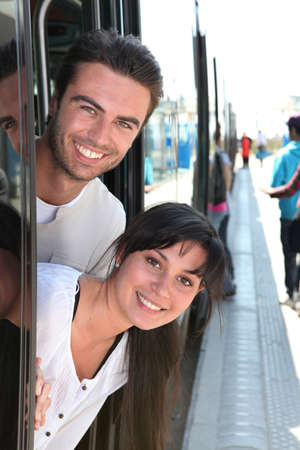 25 30 years women: Couple leaning out of a tram door at a station Stock Photo