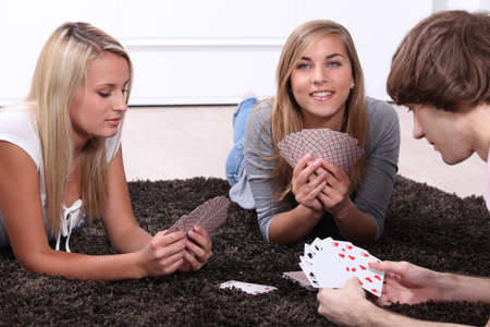 jeu de cartes: Trois adolescents assis jouant un jeu de cartes
