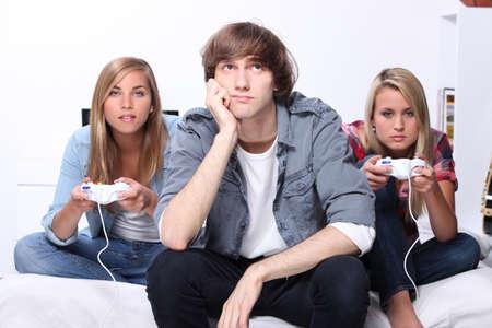 Trois adolescents jouant le jeu d'ordinateur Banque d'images