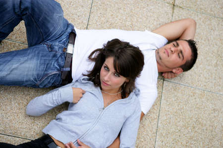 Couple laying on pavement photo