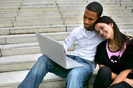 Couple sitting on some steps with a laptop photo