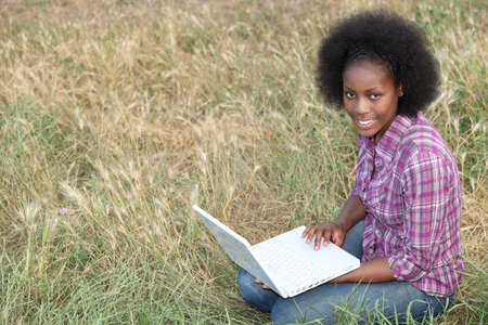 young Afro-American woman sitting on the grass with her laptop Stock Photo - 12006630