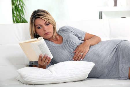 mother to be: Donna incinta sdraiata su un divano a leggere un libro