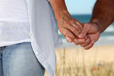 Married couple walking along beach photo