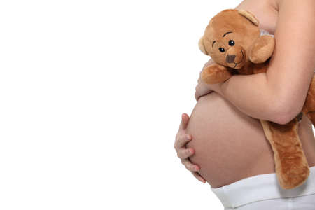 Pregnant woman holding a teddy bear photo