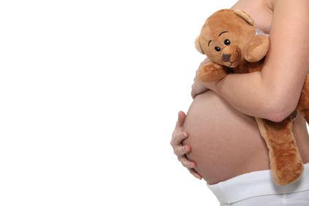 8 9 months: Pregnant woman holding a teddy bear
