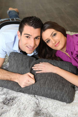 a couple lying on a carpet photo