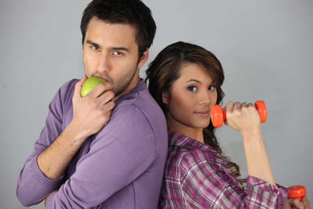 Young man with an apple and woman with a dumbbell photo