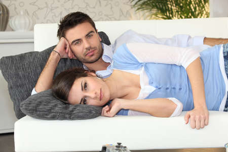 poker faced: Couple lying on a couch together Stock Photo