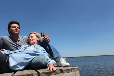 40 45: Couple relaxing by the lake Stock Photo