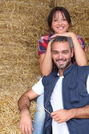 Farmer couple sitting amongst hay bales photo