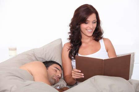 woman bed: Mujer leyendo en la cama como su pareja duerme