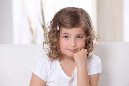 Young girl sitting on a sofa photo