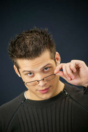 difficult task: Young man removing his eyeglasses