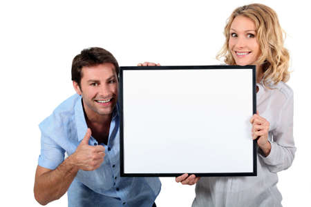 holding a sign: Couple holding up a blank sign
